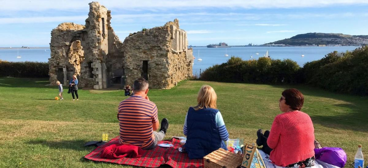 Three people having a picnic at Sandsfoot Castle, Weymouth, Dorset
