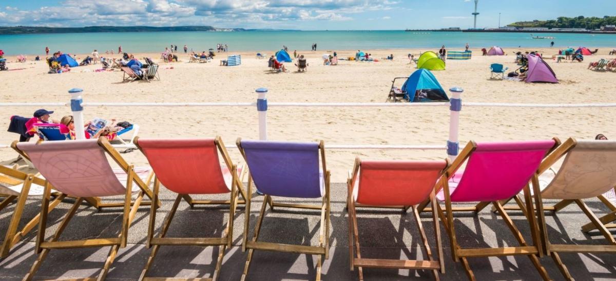 Colourful deckchair on the promenade at Weymouth Beach, looking onto the beach