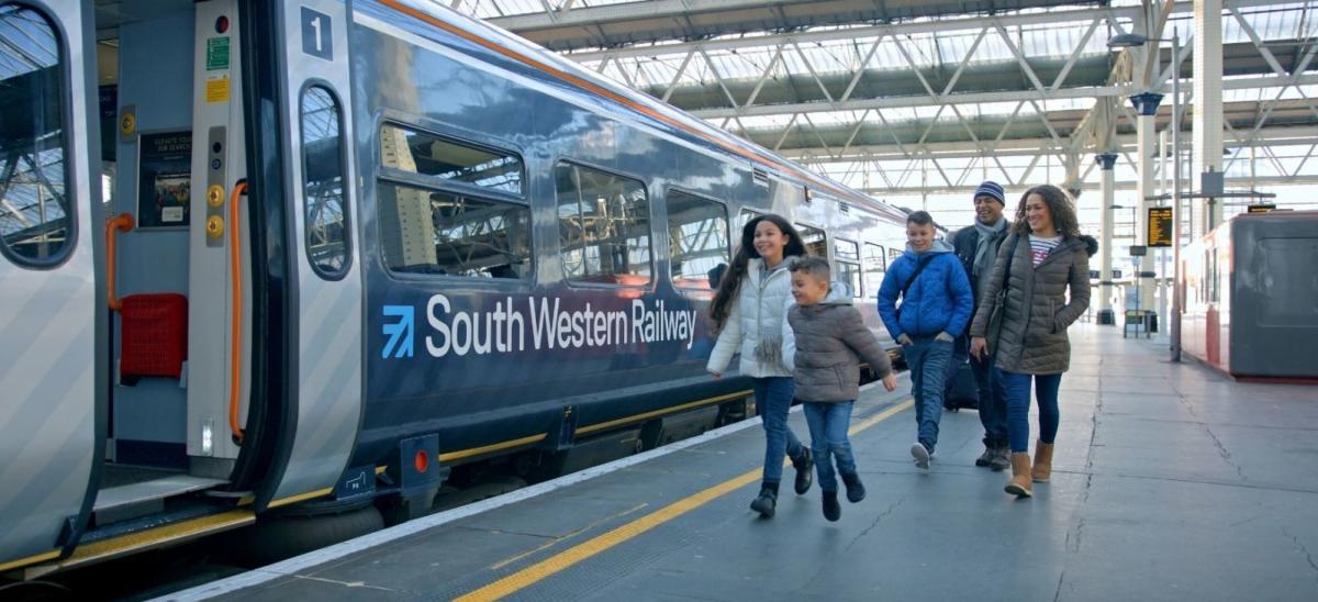 Family boarding a South Western Railway train