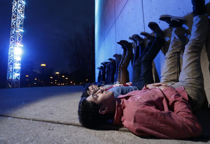 Students laying on the ground at night with their legs propped up against the IU Art Museum as the Light Totem colors change