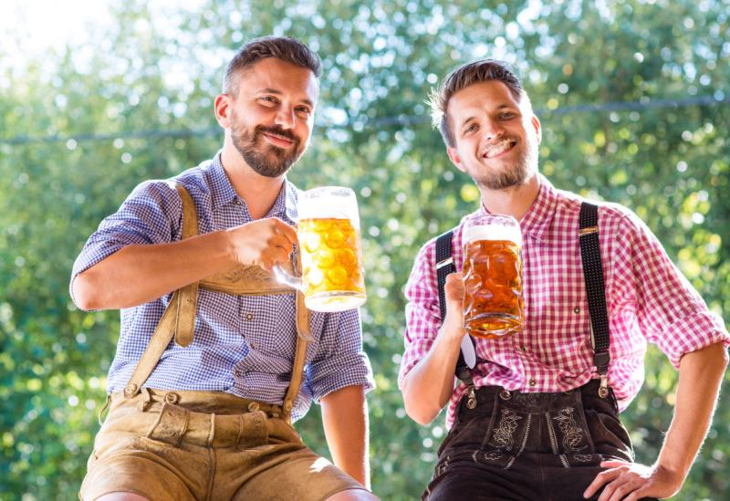 Two 20-something men in short sleeve shirts and lederhosen raise their glass steins full of beer for a toast