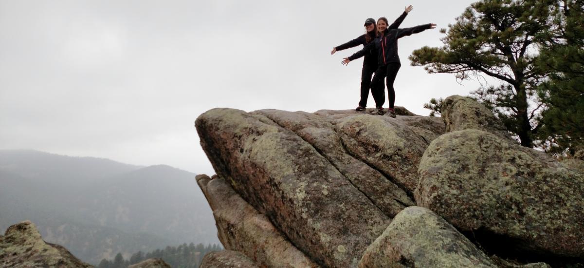 Women on posing on top of rocks on a winter hike in Boulder