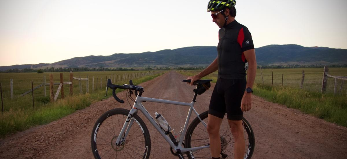 Thomas standing on dirt road with gravel bike
