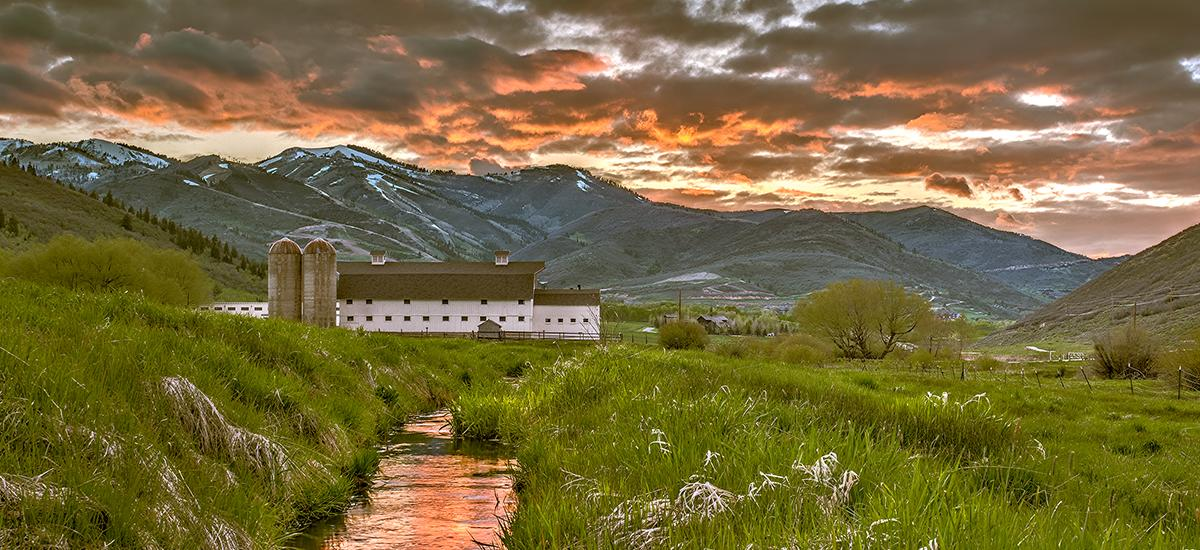 Scenic of a White Barn during a colorful Spring Sunset with mountains in the background