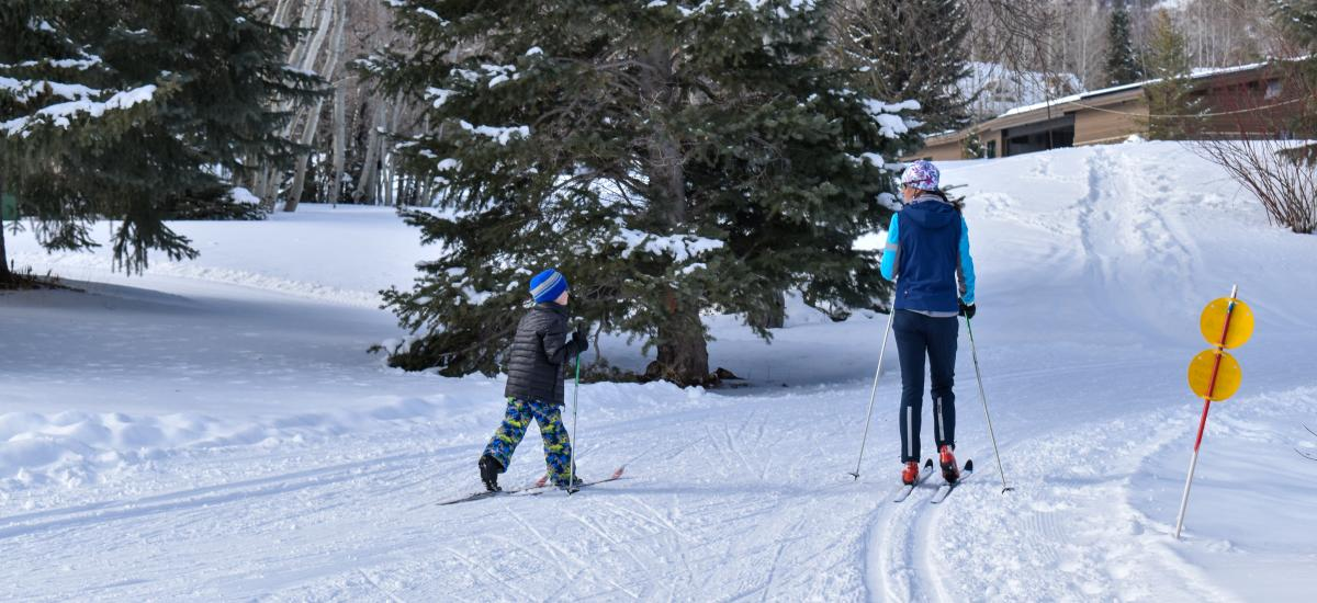 Young boy learning how to nordic ski with instructor