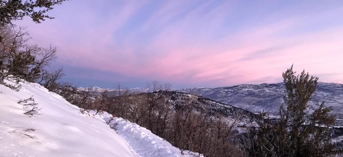 A colorful sky and snowy trail during sunrise in winter