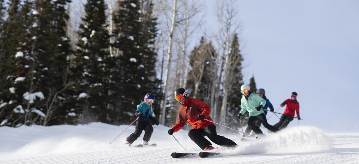 Family skiing down groomer run