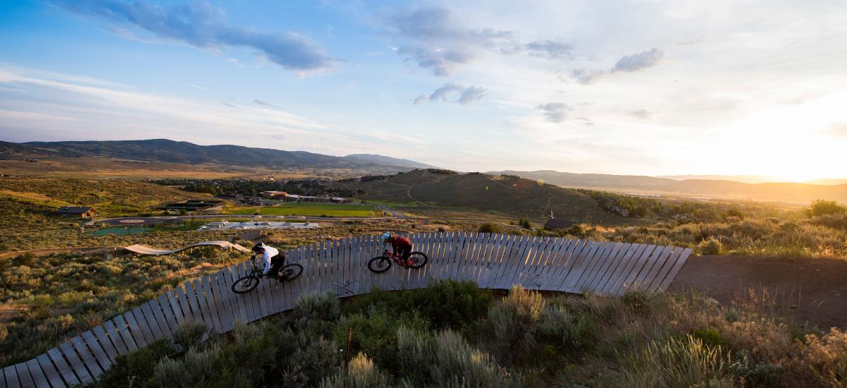 Two mountain bikers riding a rainbow rail in bike park