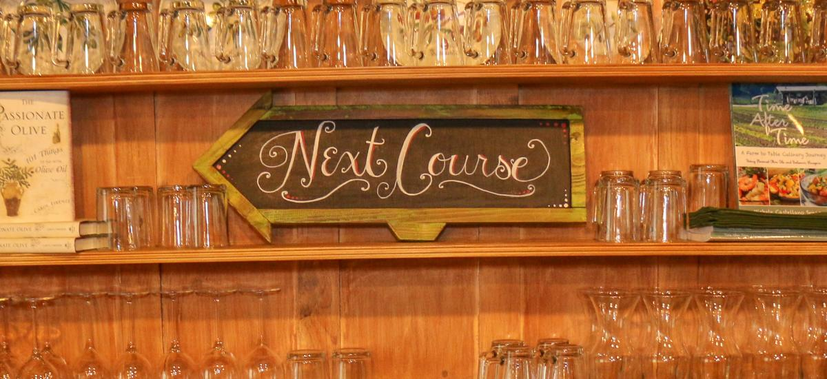 Glassware and a sign that reads Next Course