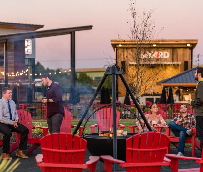 People sitting around a fire in red Adirondack chairs, in the back there is a building and an outdoor stage
