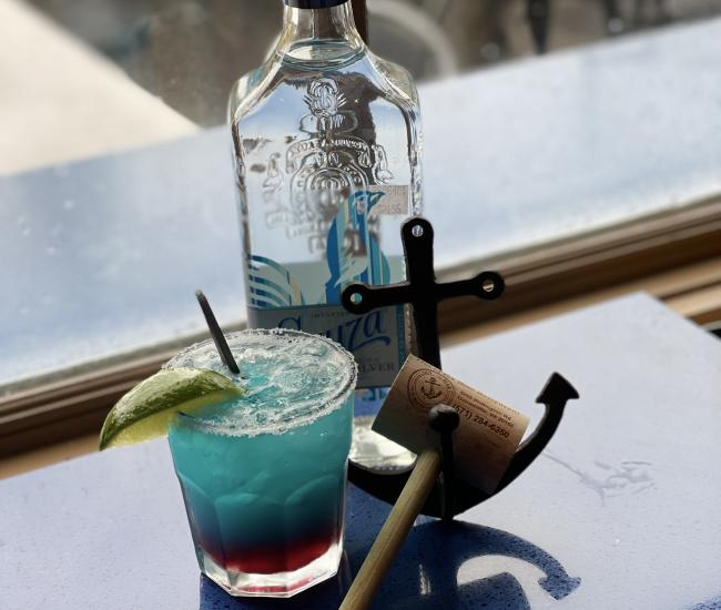 blue cocktail, spirit bottle and crab hammer on a window sill