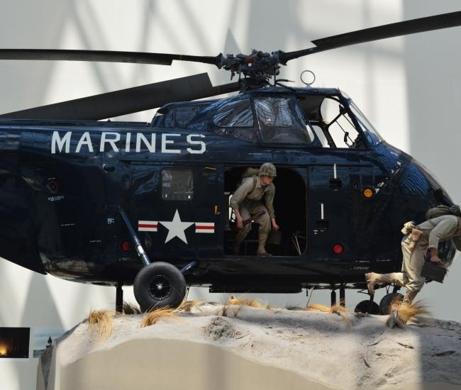 "a navy helicopter with the word ""marines"" on the front with 2 statues of men coming out of the helicopter"