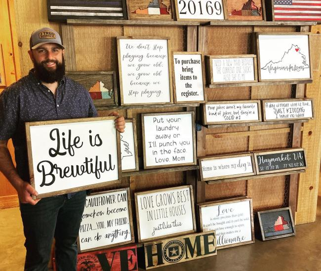 J Tred Woodworking Signs - man holding sign in front of a display wall of wooden signs