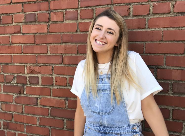 Rebekah Gregg poses for a photo against a brick backdrop