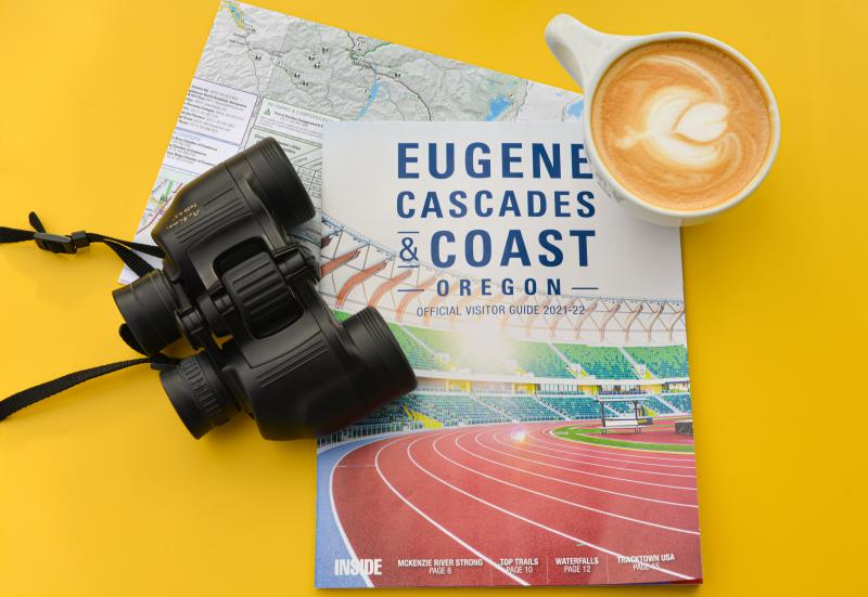 Eugene cover visitor guide with binoculars and coffee