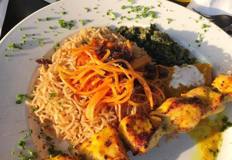 A chicken kebab plate with rice from Samira