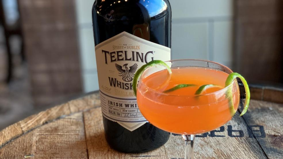 A bright orange cocktail with a lime peel staged in front of a bottle of Teeling Irish Whiskey