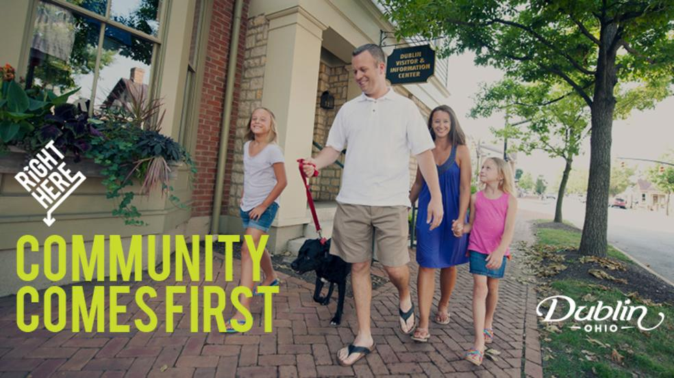 Family of four walking down the brick streets in Historic with their dog.