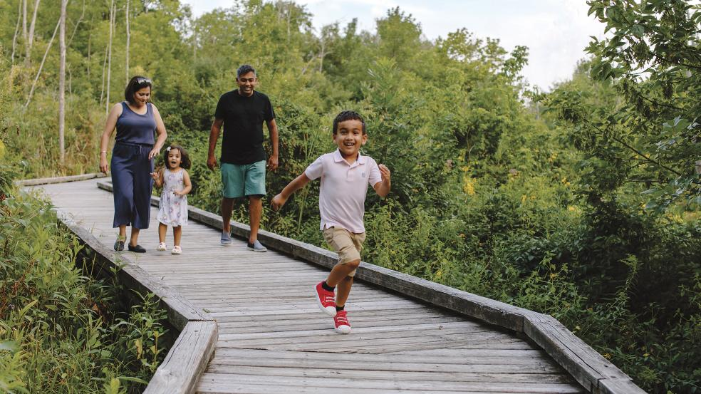 Kid running in front of his family on the boardwalk at Kiwanis Riverway Park