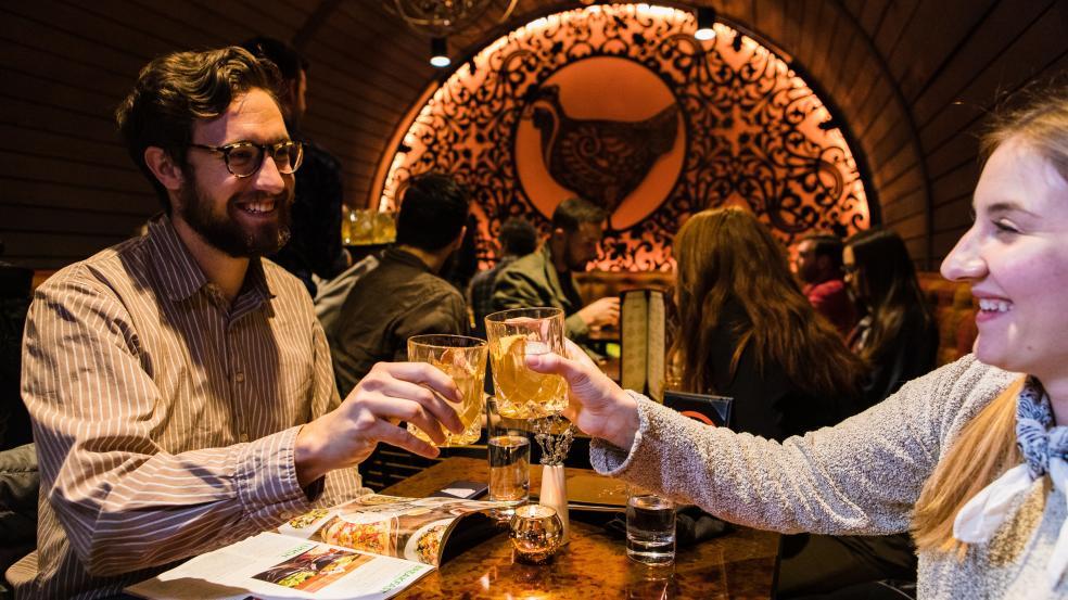 Couple cheersing cocktails in the orange barrel room at Hen Quarter.