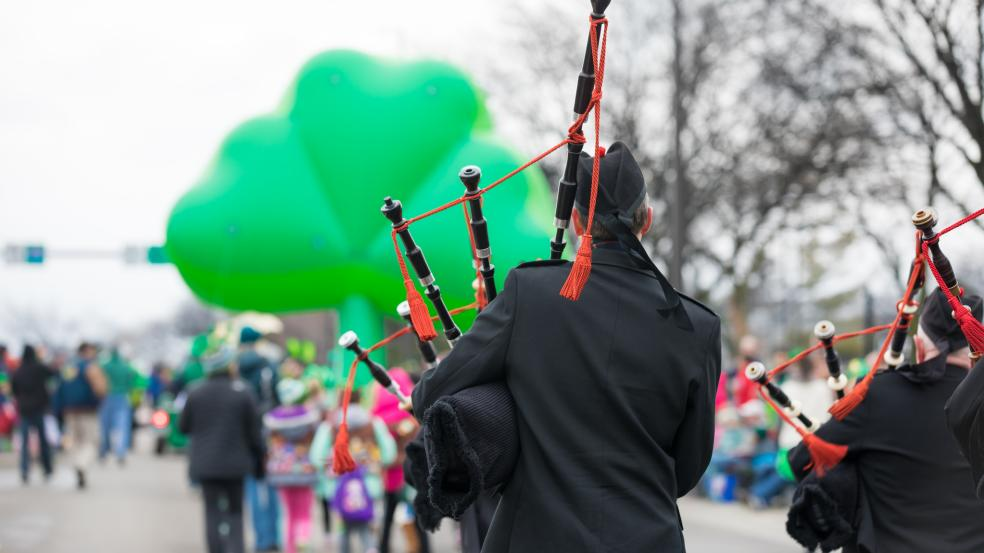 St. Patrick's Day Parade Bagpiper walking behind a giant green shamrock balloon.