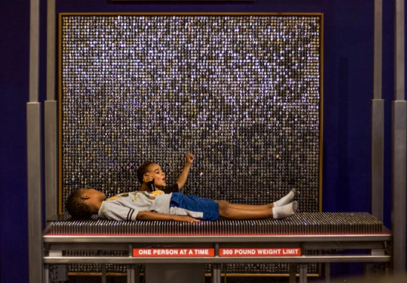 Two little boys exploring a bed of nails exhibit at WonderLab Museum