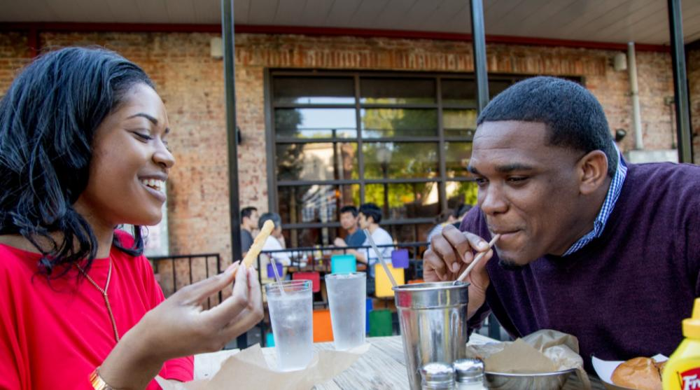 Smiling couple enjoying food and drink in an outdoor patio in Athens, GA