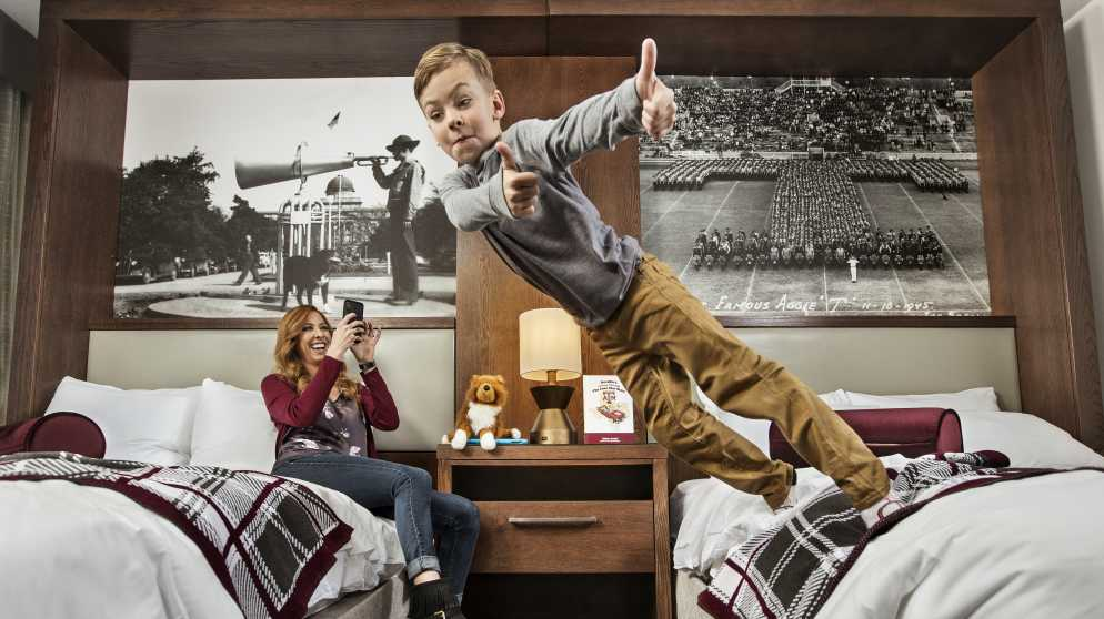 TAMU Hotel Kid Jumping On Bed