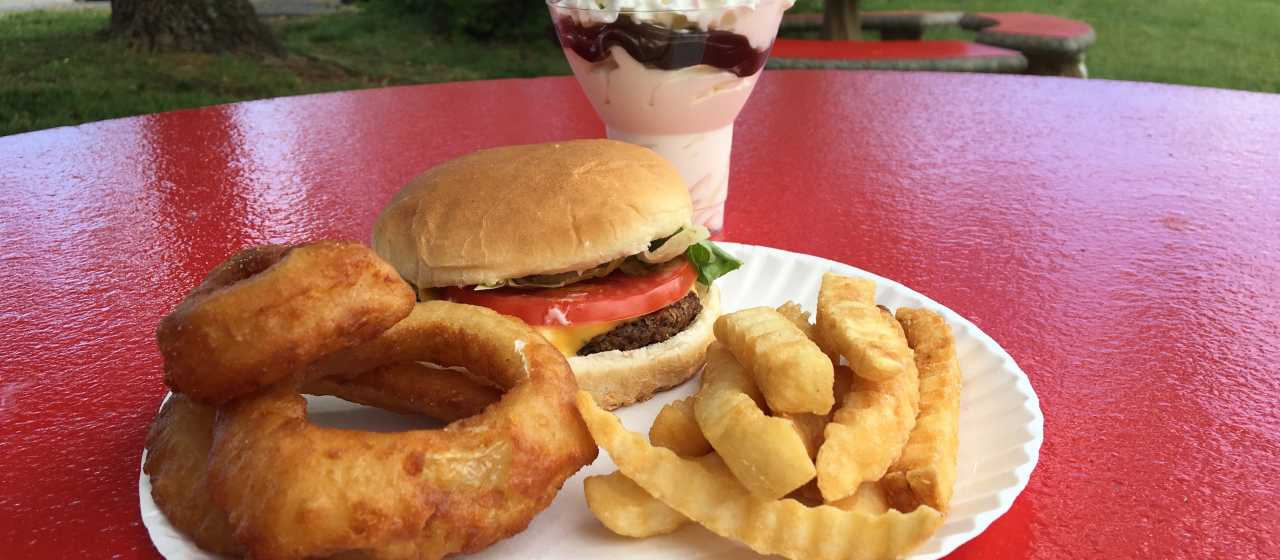 A local joint serves up a cheeseburger with onion rings & crinkle-cut fries and an ice cream sundae.}