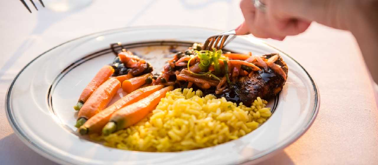 Woman's hand holding a fork over a plate of food with carrots, rice and chicken}