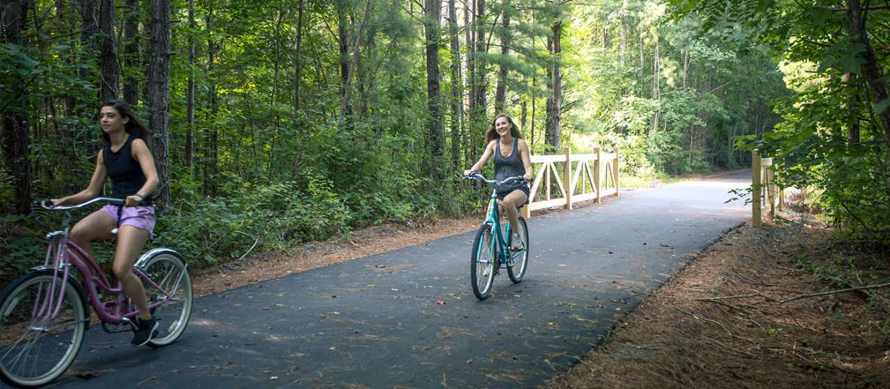 Two women right their bicycles along a forested section of the Thermal Belt Rail Trail in Rutherford County, NC.}