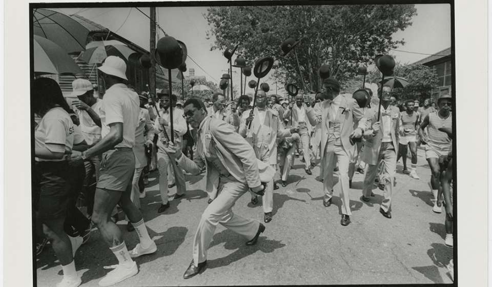 "Richard ""King"" Matthews (foreground) leads the inaugural parade of the Avenue Steppers Marching Club's in 1982, as seen in this photograph by Michael P. Smith."