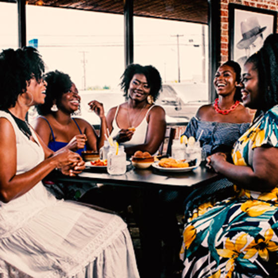 group of black women enjoying a meal at a restaurant