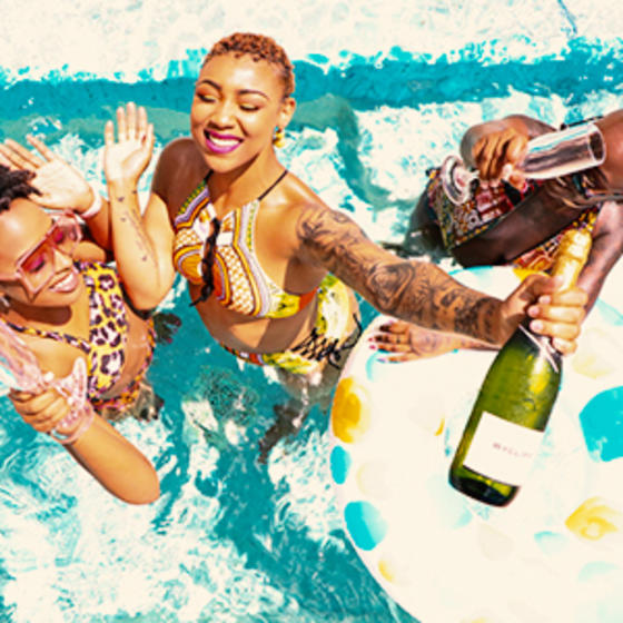 group of black women enjoying cocktails in a swimming pool