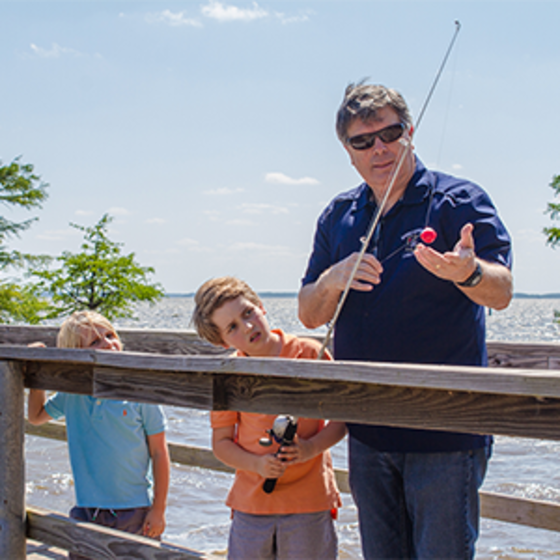 Man and grandsons fishing from lake pier at Caddo Lake
