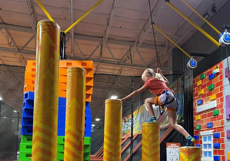 A girl climbing an obstacle course at Urban Air