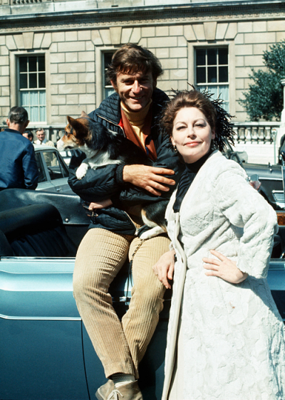 Roddy McDowall holding Ava's corgi standing next to Ava Gardner in front of a car on set of Tam Lin in London.