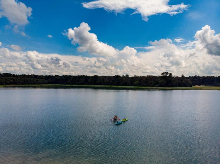 A drone shot of 3 colorful kayaks in a lake with a blue sky.
