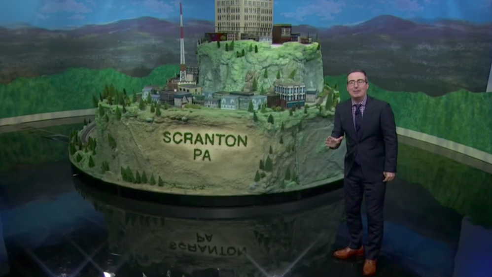 John Oliver standing in front of the Scranton train set.