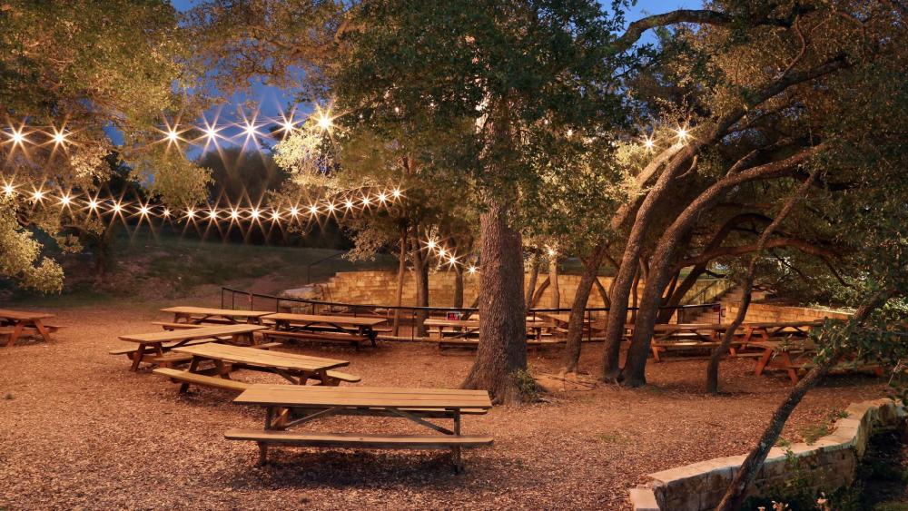 Photo of the outdoor Beer Garden at Live Oak Brewing at night. String lights twinkle from the trees above several empty wooden picnic tables