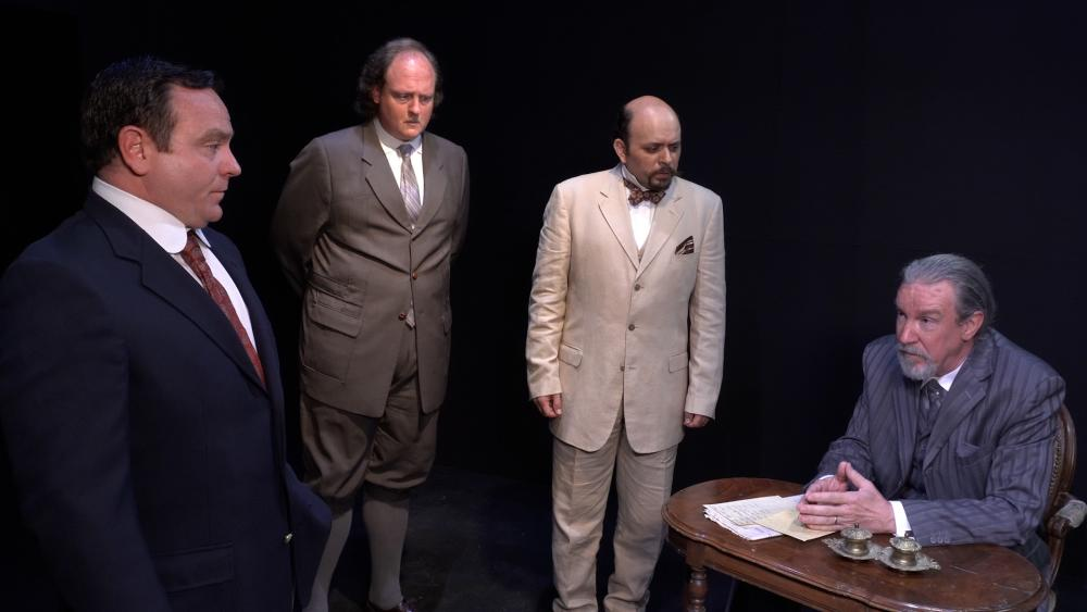 Agatha Christie's The Mysterious Affair at Styles, at Austin Playhouse. The photo pictures four men wearing suits, the man playing Hercule Poirot has a curled moustache