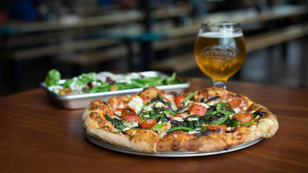 Small pizza with tomatoes and spinach in front of a tulip beer glass and a green salad at Pinthouse Pizza