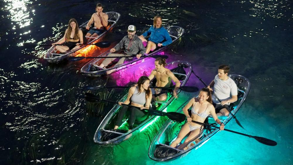People paddling in clear kayaks at night with colored lights