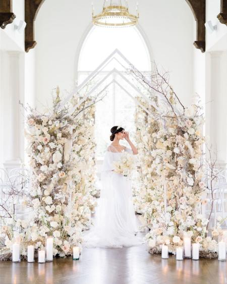 A bride stands in front of a floral arch.