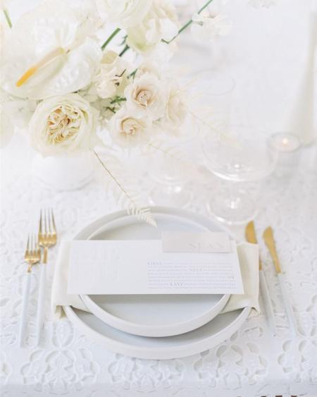 A white place setting at a wedding reception