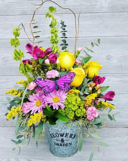 A rose, daisy and carnation flower bouquet in a metal bucket.