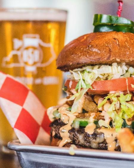 tall burger with a glass of beer behind it at 859 taproom and grill in florence ky