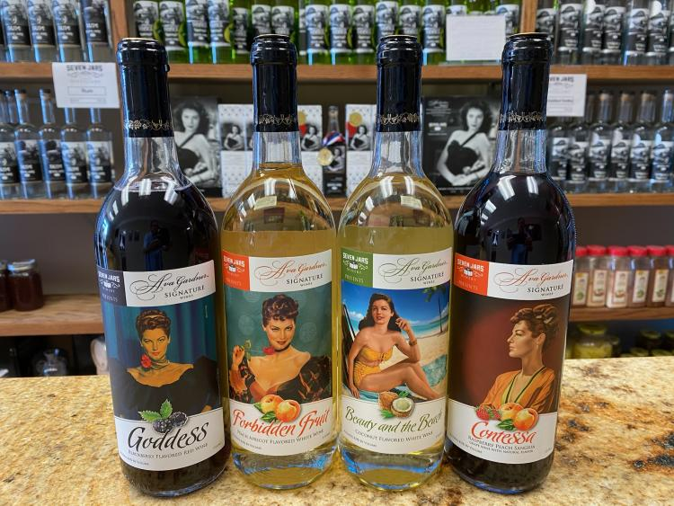 Four bottles of wine from the Ava Gardner Signature Wine Collection, lined up on a bar in front of shelves of alcohol at Seven Jars Distillery.