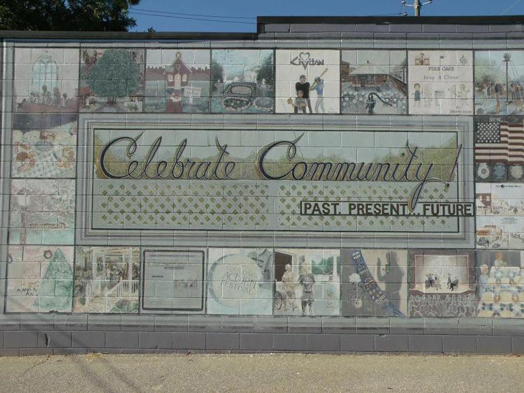 Mural with historic depictions and Celebrate Community in the center in Four Oaks