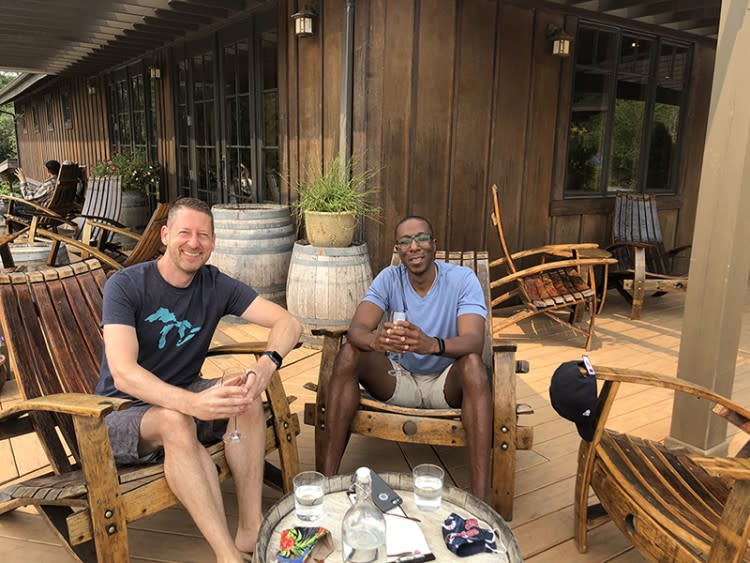 A smiling multiracial gay couple enjoy the patio at Coeur de Terre winery.